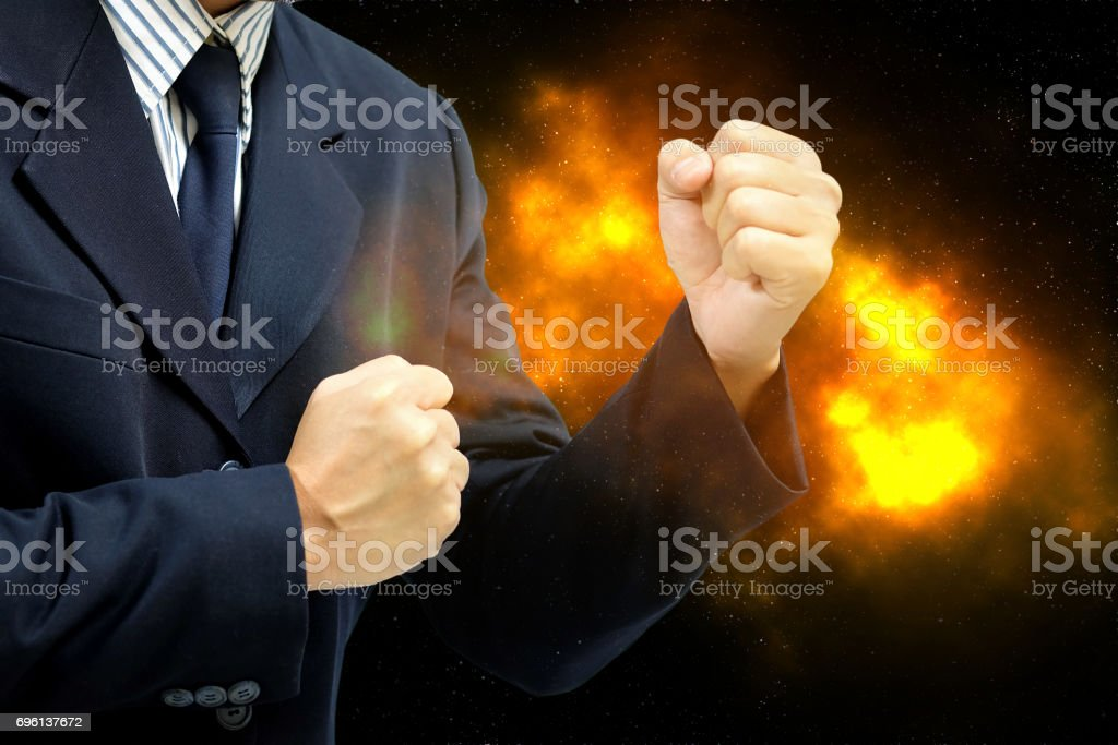 Business Man wearing a suit fists ready to fight. , The concept of business competition is fierce as fire. stock photo