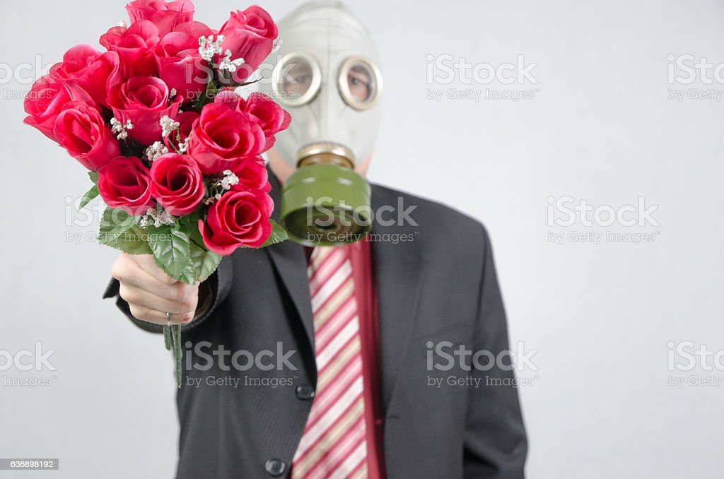 Business man wearing gas mask and holding bouquet of roses stock photo