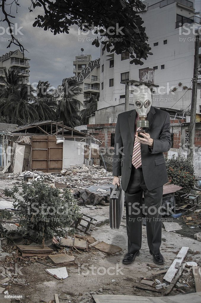 Business man wearing gas mask and looking at cell phone stock photo