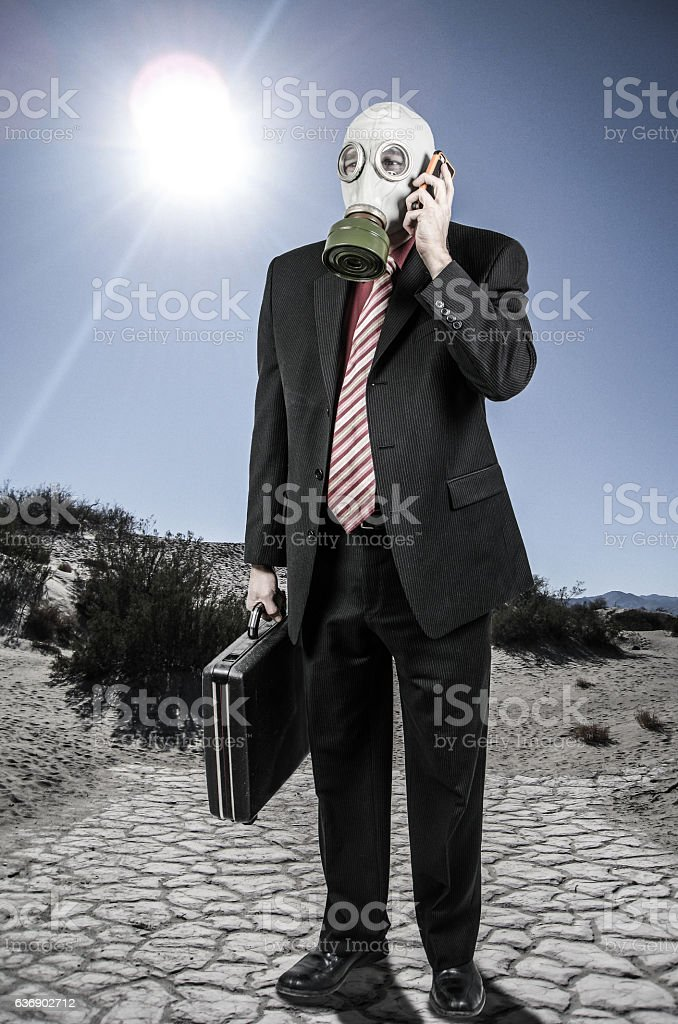 Business man wearing gas mask talking cell phone in desert stock photo