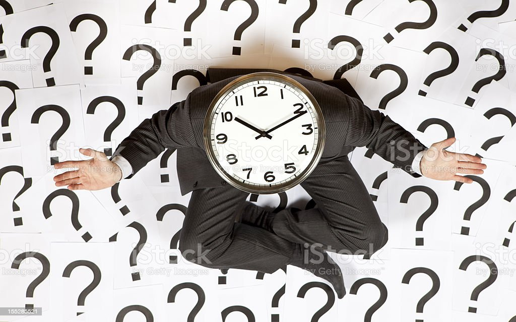 Business man with a clock head surrounded by question marks royalty-free stock photo