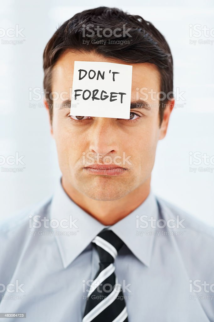 Business man with a 'don't forget' sign on forehead royalty-free stock photo