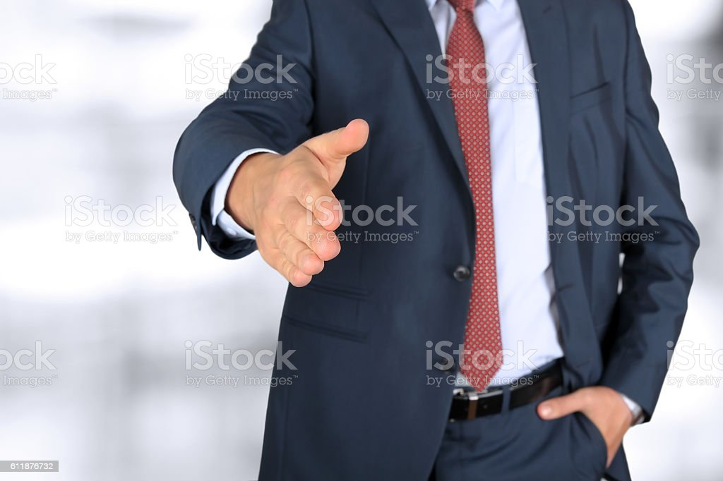 Business man with an open hand extended to handshake stock photo