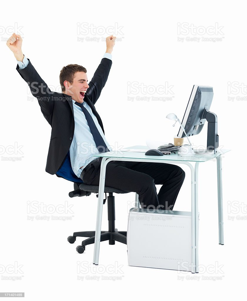 Business man with arms raised in excitement at office desk isolated on white background royalty-free stock photo