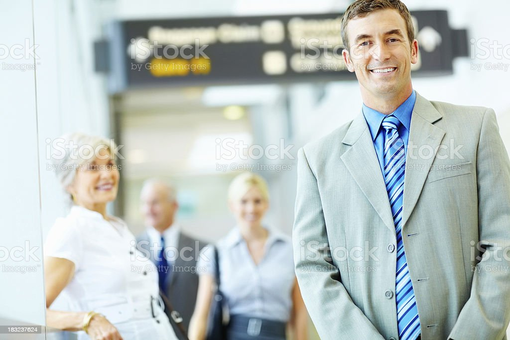 Business man with businesspeople in background at airport royalty-free stock photo
