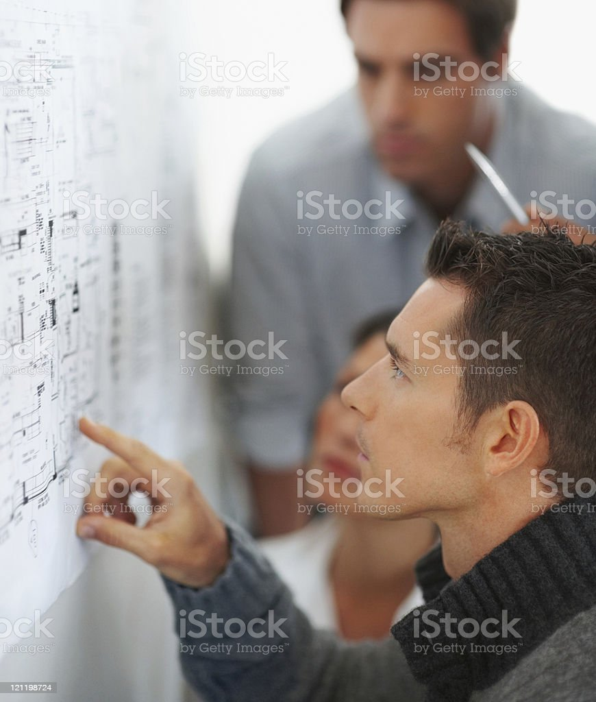 Business man with colleagues studying a chart on the wall royalty-free stock photo