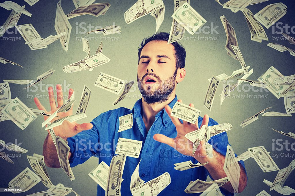 business man with eyes closed trying to catch dollar bills stock photo
