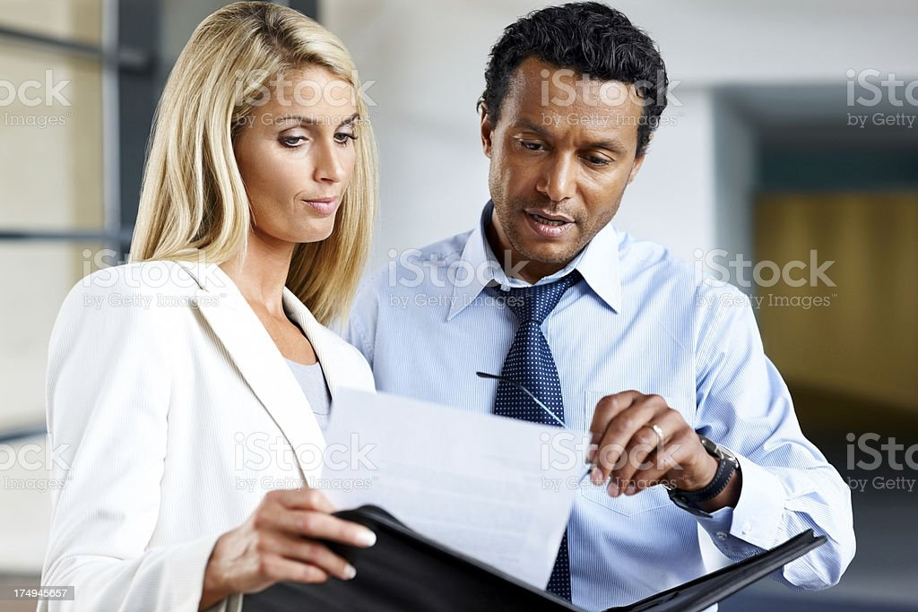 Business man with female colleague going through a document stock photo