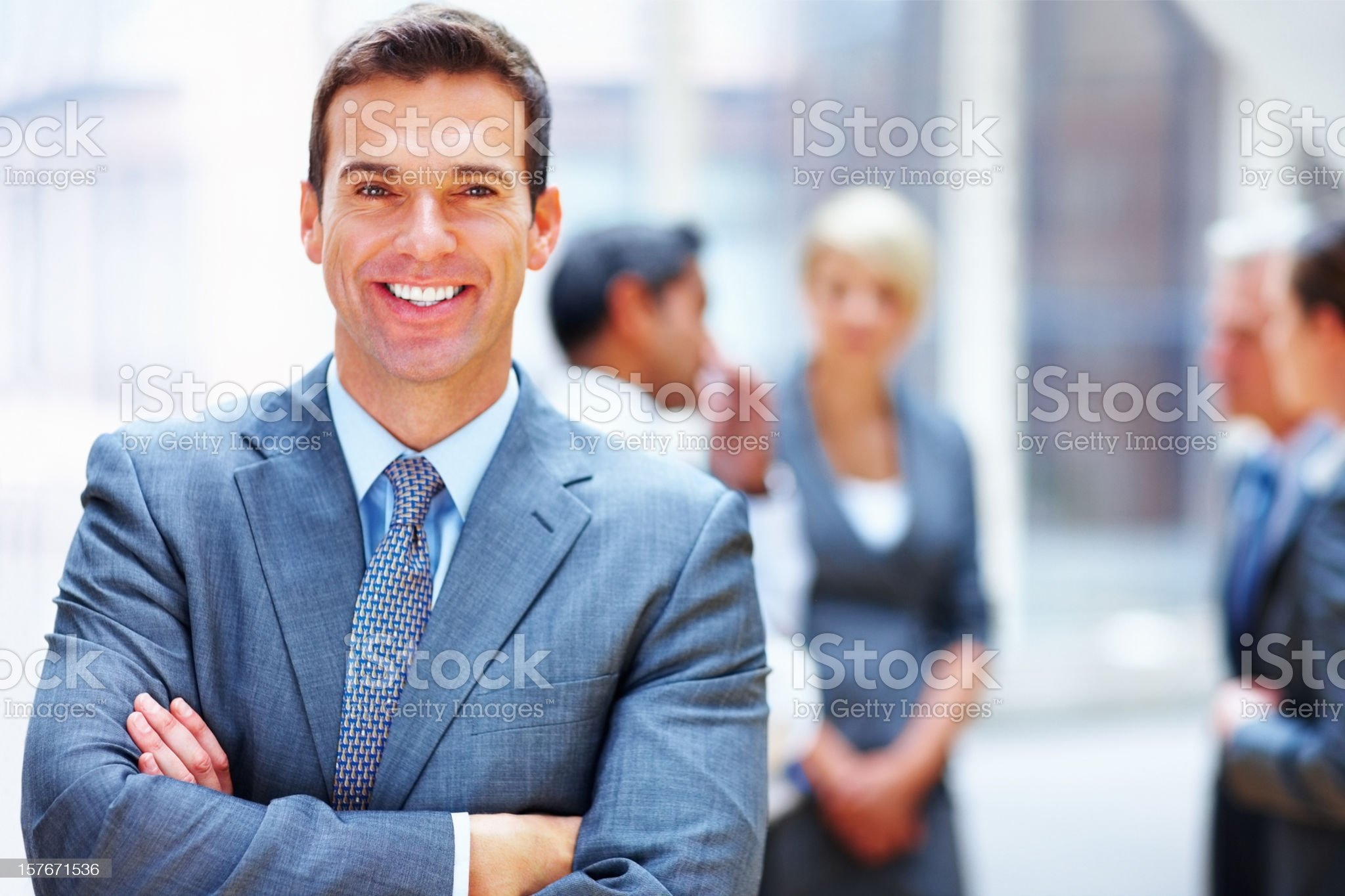 Business man with hands folded and his team in background royalty-free stock photo