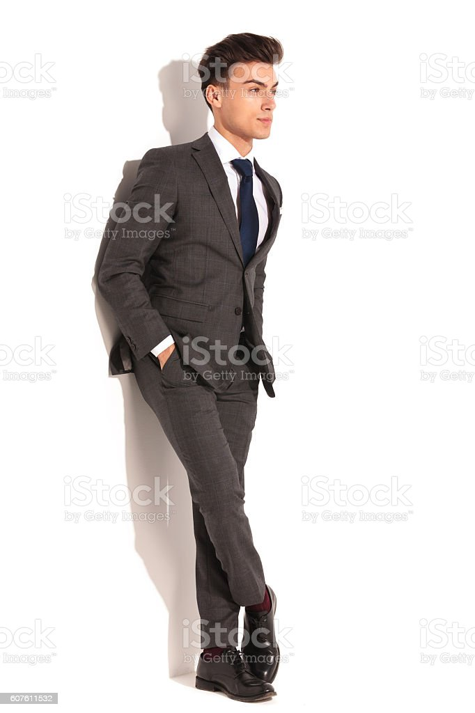 business man with hands in pockets and legs crossed stock photo