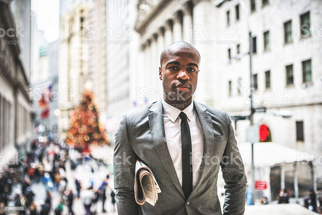 business man with his newspaper on wall street stock photo