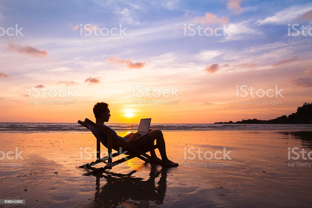 business man with laptop working on the beach stock photo