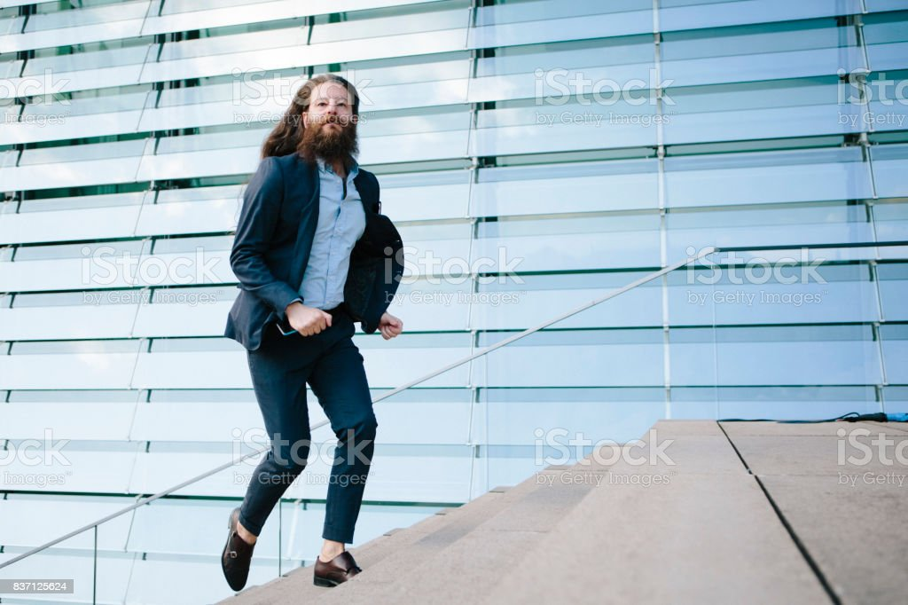 Business man with long hair and beard running stairs high stock photo