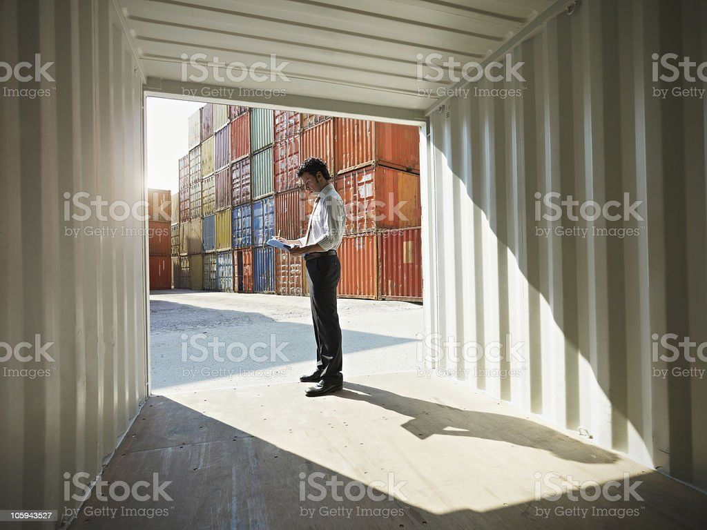 business man with shipping containers stock photo
