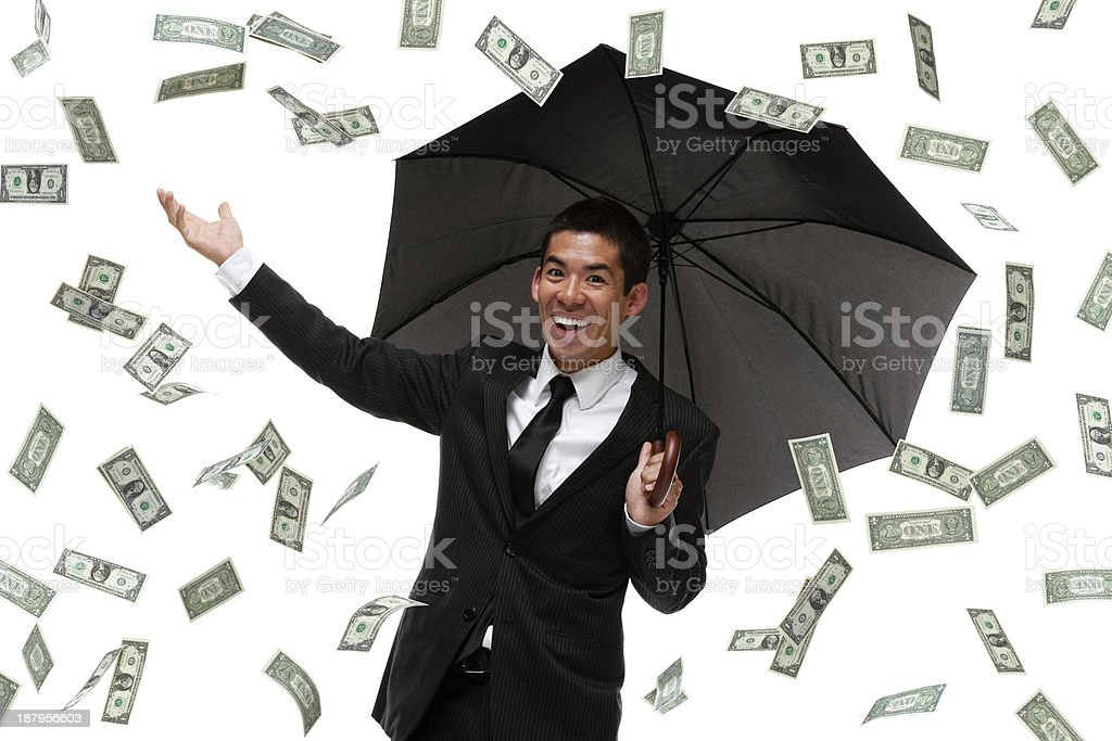 Business man with umbrella in money rain storm stock photo