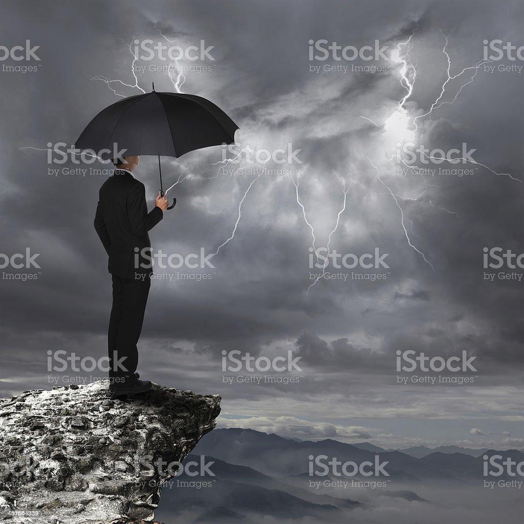 Business Man with umbrella look rainstorm cloud stock photo