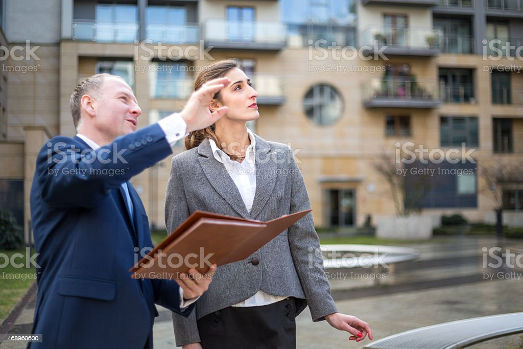 Business man with woman looking and pointing up stock photo