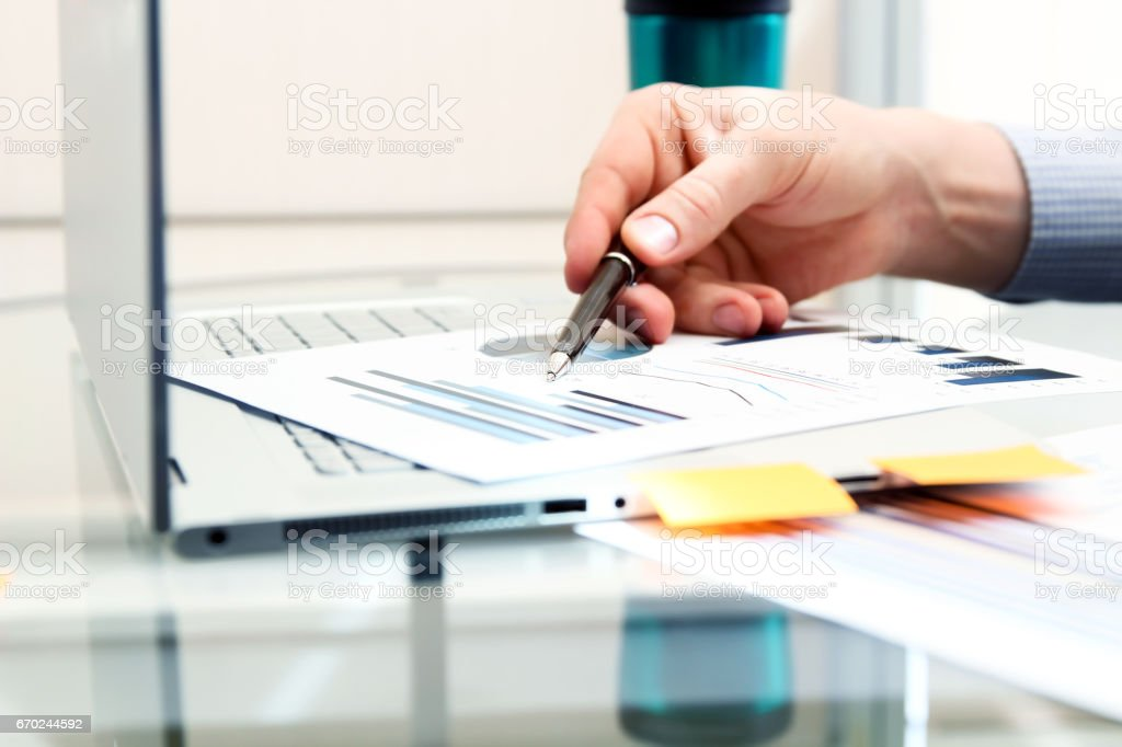 Business man working and analyzing financial figures on a graphs using laptop stock photo