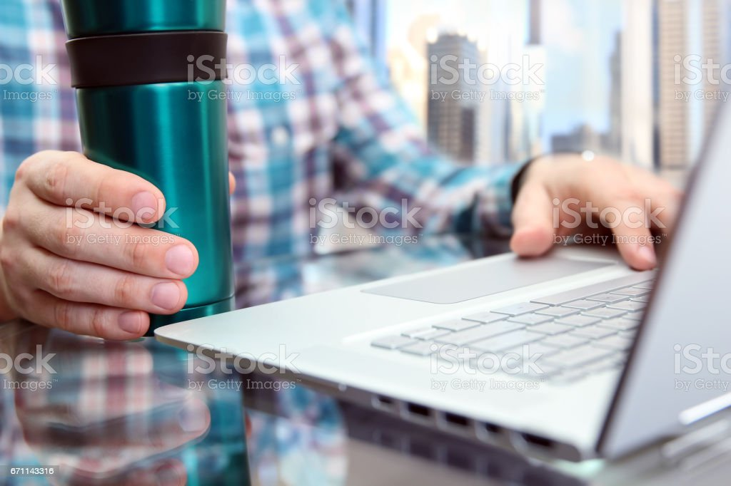business man working and analyzing financial figures using laptop in the office with cofee or tee stock photo