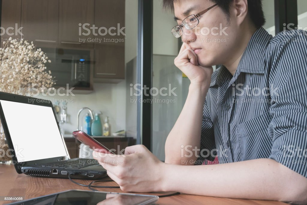 business man working from home with mobile phone and laptop computer stock photo