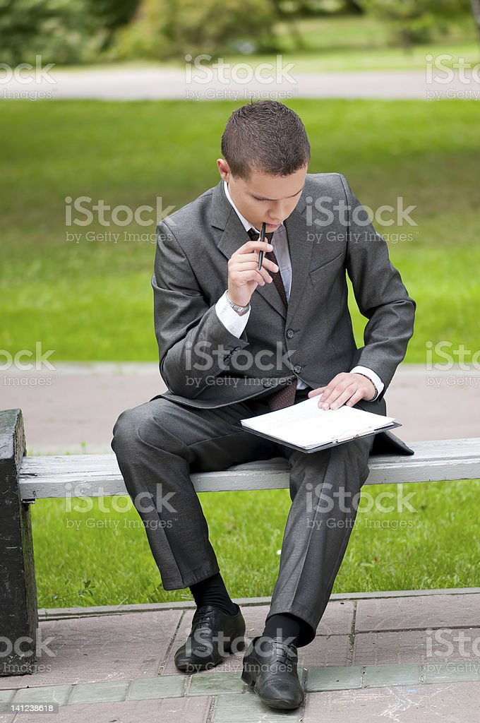 business man working with papers at park. Student stock photo