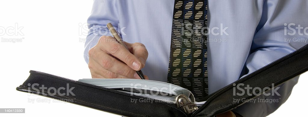Business man writing in leather organizer stock photo