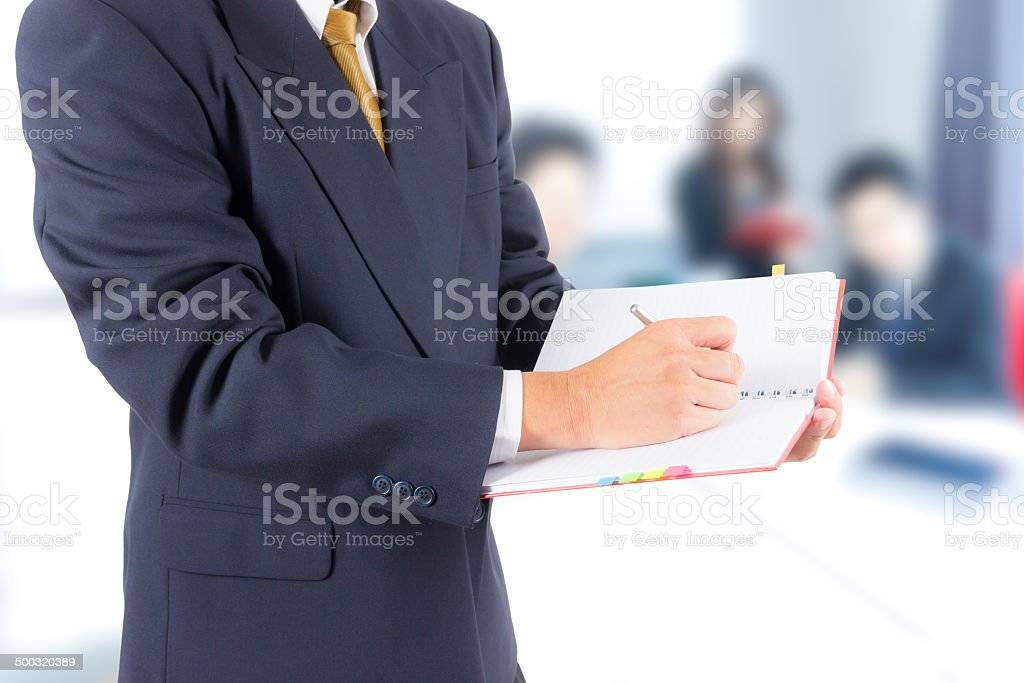 business man writing on notebook stock photo