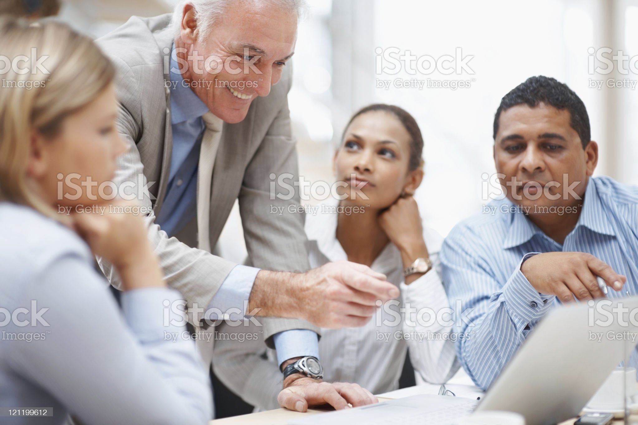 Business manager discussing a new project on laptop with team royalty-free stock photo