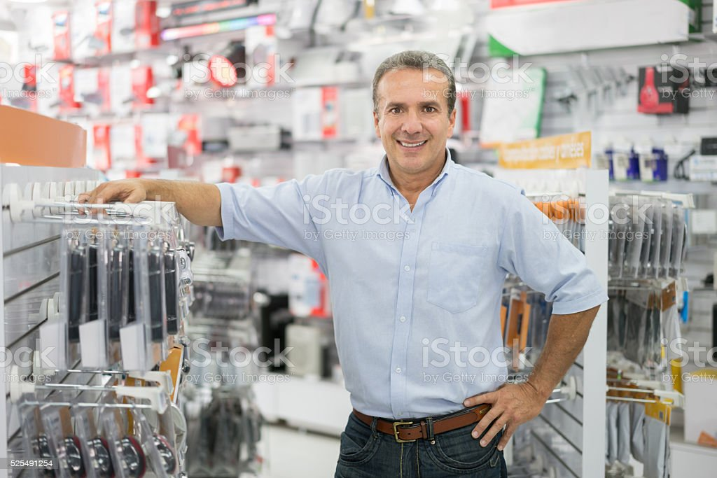Happy business manager running a tech store and looking at the camera...