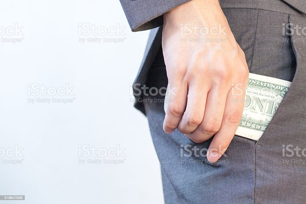 Business man's hand hiding money in pocket stock photo