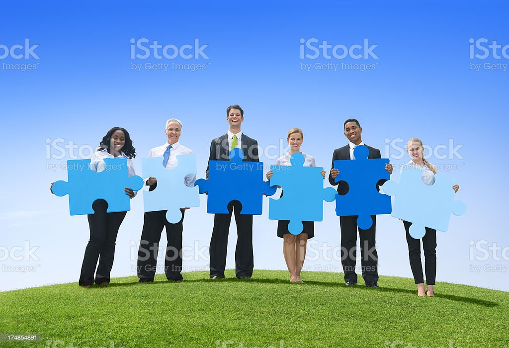 Business men and women holding puzzle pieces in a field stock photo