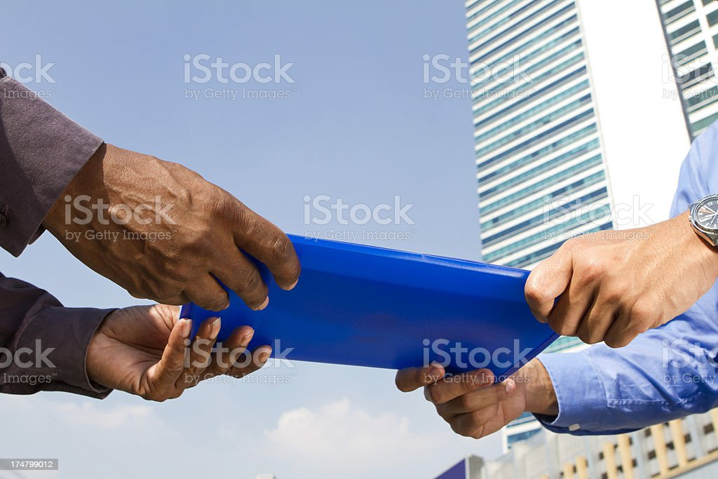 Business men handing over a file report in financial district royalty-free stock photo