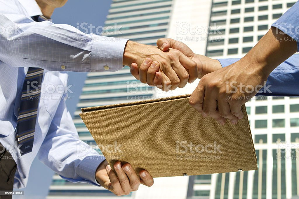 Business men handshaking and sharing file report in financial district stock photo