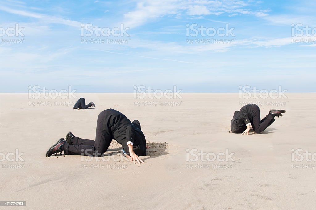 Business men hiding head in sand stock photo