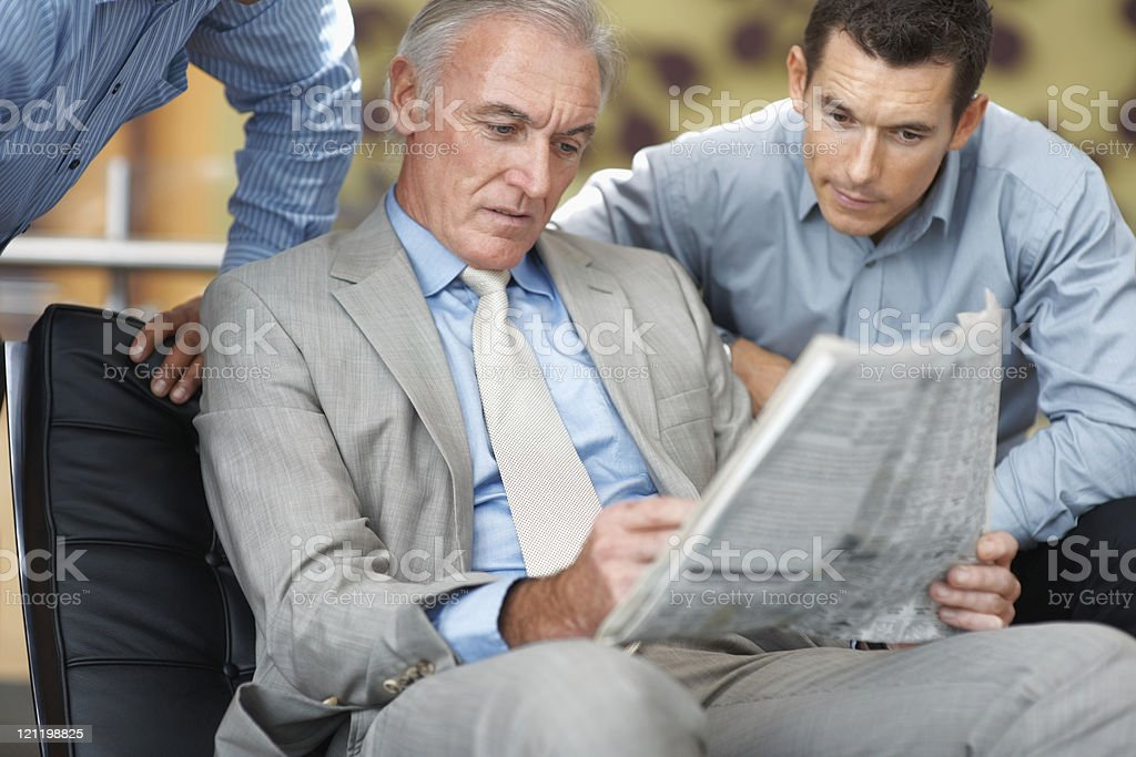 Business men interestingly reading a newspaper at work royalty-free stock photo