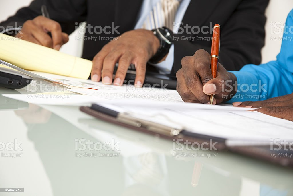 Business men taking notes at office meeting. African descent. Paperwork. stock photo
