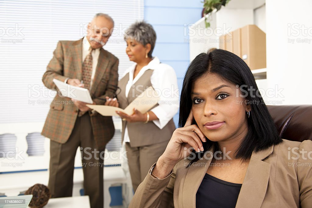 Business: Multi-ethnic coworkers, brunette woman in foreground royalty-free stock photo
