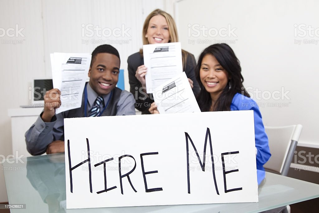 Business: Multi-ethnic people with job applications and 'hire me' sign royalty-free stock photo