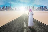 Business muslim using smartphone on road
