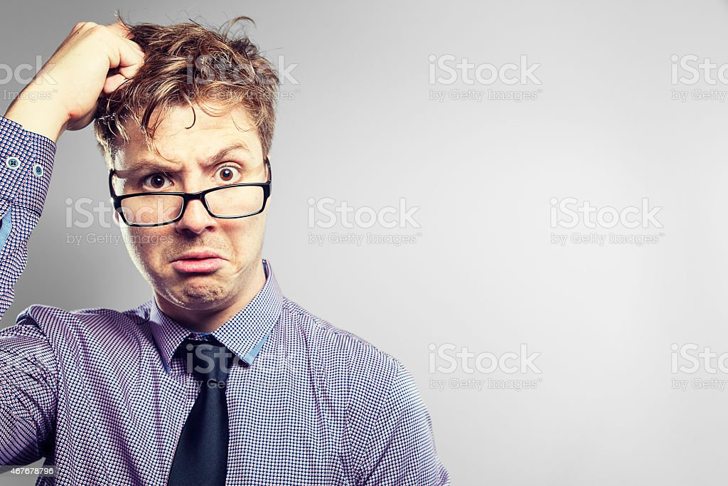 Business nerd scratching his head and looking at camera stock photo