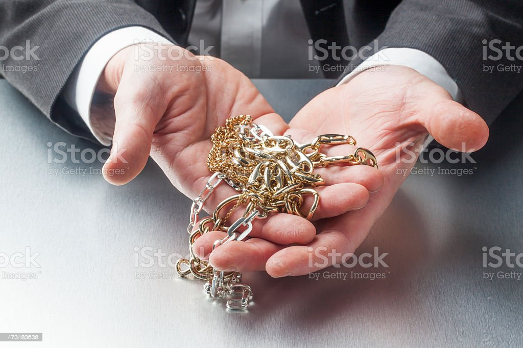 business of appraiser with golden jewelry in hands stock photo