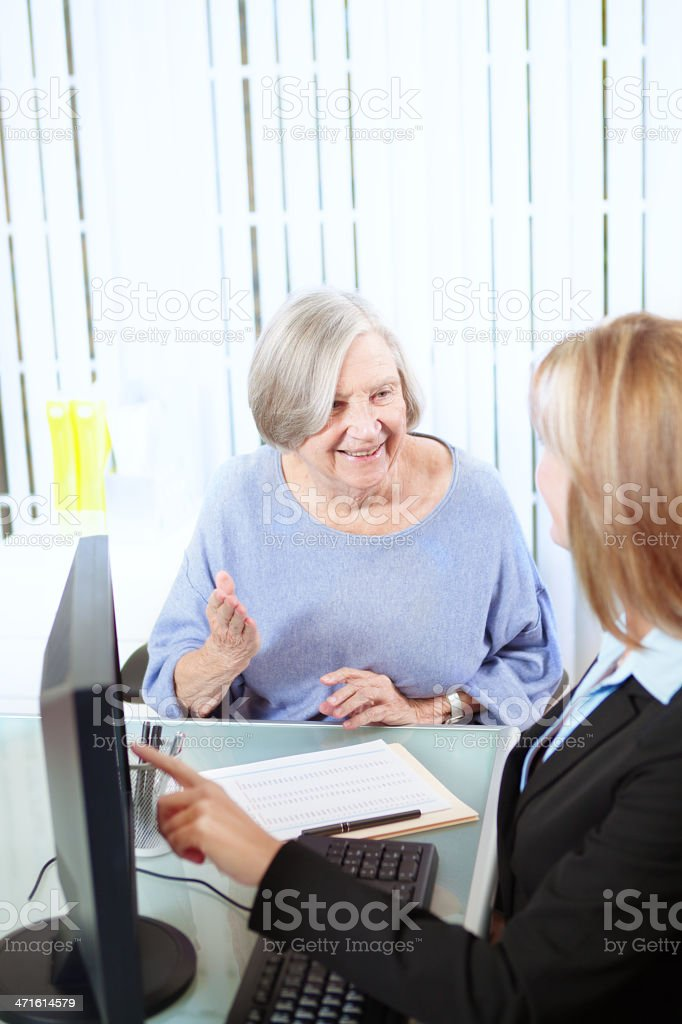 Business Office Professional Woman at Computer Helping Senior Female Customer royalty-free stock photo