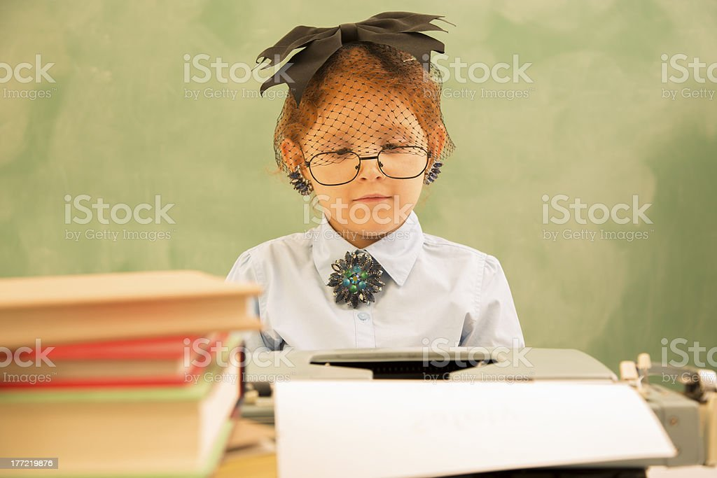 Business:  Old-fashioned office.  Child typing on typewriter. Secretary. royalty-free stock photo
