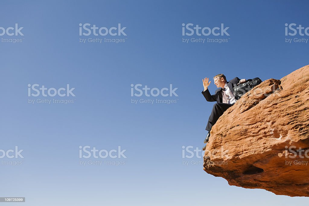 Business Outlook: forward-looking businessman sitting near a precipice stock photo