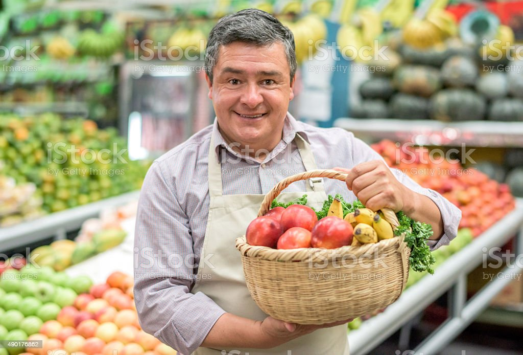 Business owner at a food market holding a basket stock photo