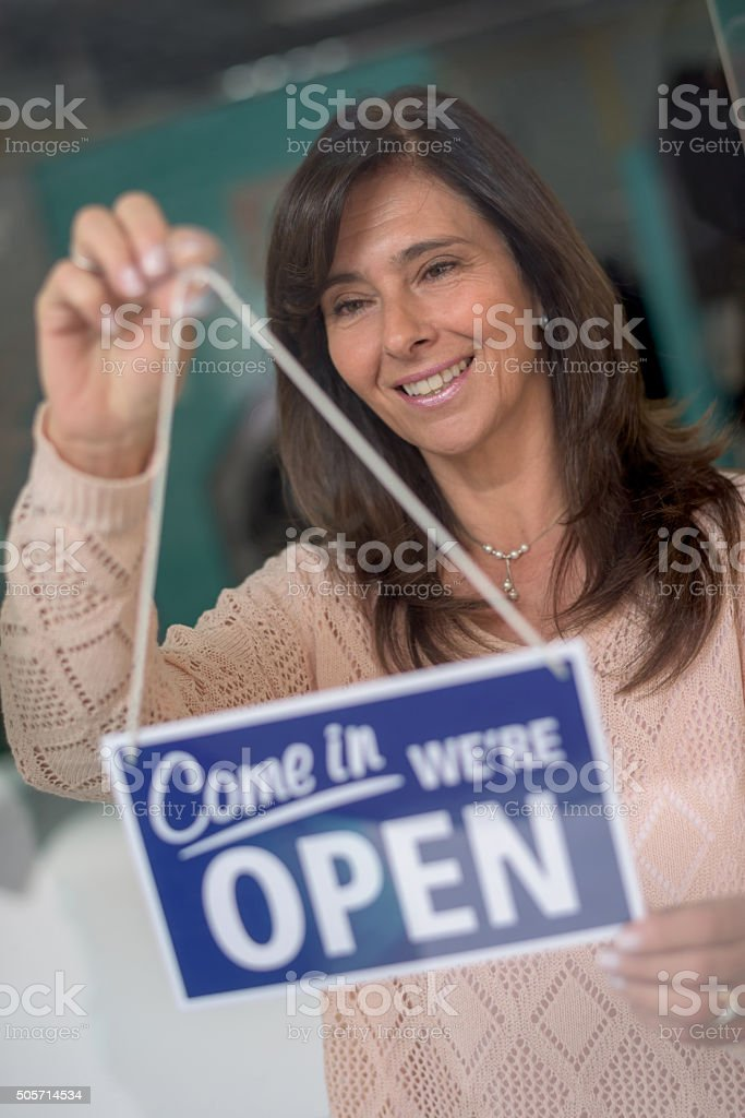 Business owner hanging an open sign stock photo
