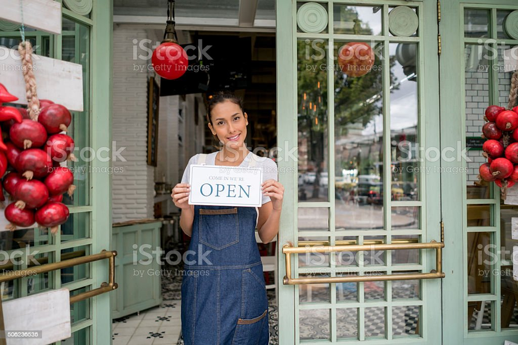 Business owner holding an open sign at a restaurant stock photo
