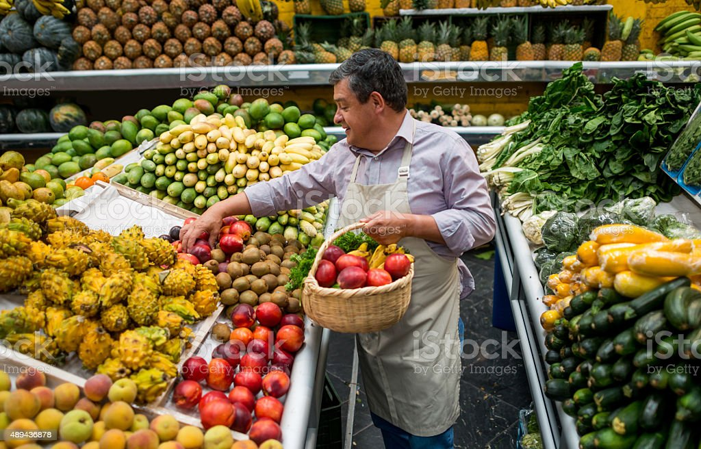 Business owner organizing fruits at a grocery store stock photo
