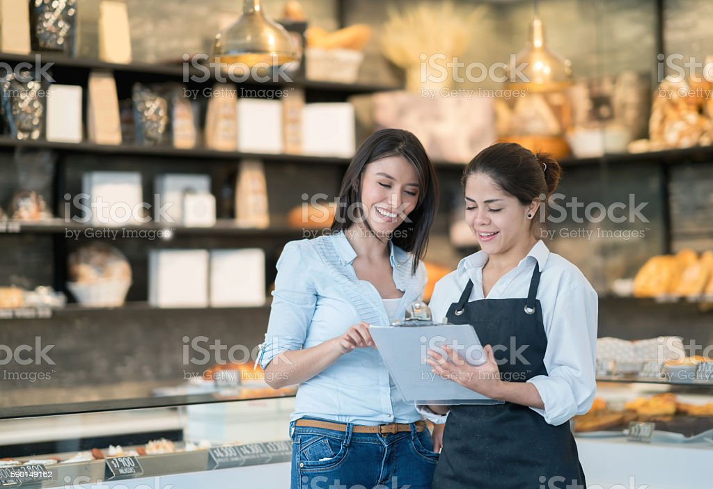 Business owner talking to worker at a bakery stock photo