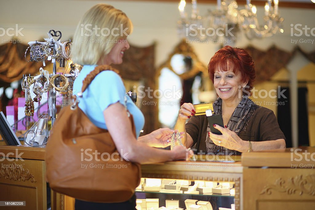 Business owner using credit card machine on cellphone stock photo